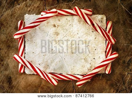 Christmas border with a red and white candie canes  around blank paper as a copy space on wooden pla