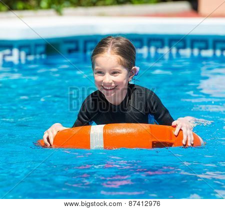 little girl swims in a wetsuit with a lifeline in the pool in  summer