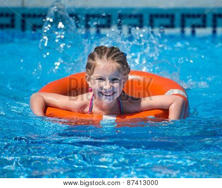 happy cute  girl swims with a lifeline in the pool in  summer