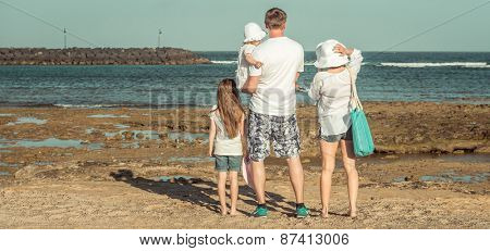 Young family of four members in the summer on the beach