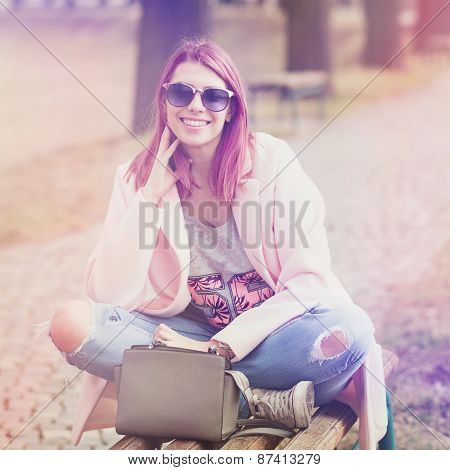 Trendy young woman with pink hair and sunglasses in park