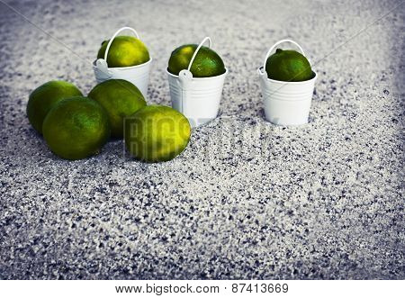 Little white buckets with limes on the sandy beach. Summer holiday concept background, travel themes