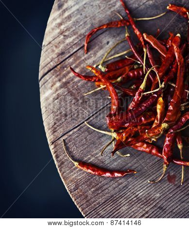 Red hot chili peppers on an old wooden table texture. Spicy pepper. Food photography with cope space
