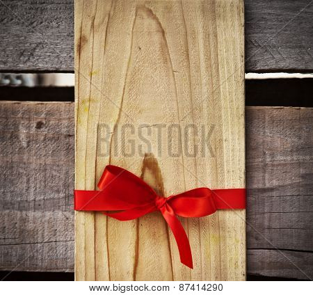 Red Bow And Blank Gift Tag With Wooden Wall