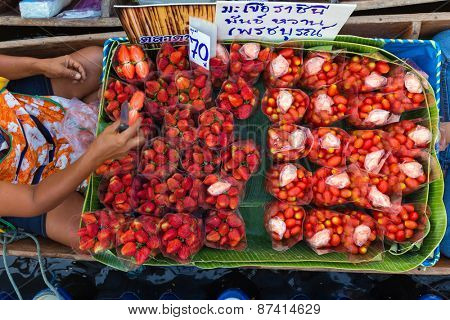 Seller of strawberries and Cherry tomatoes on a boat in a floating market in Bangkok, Thailand