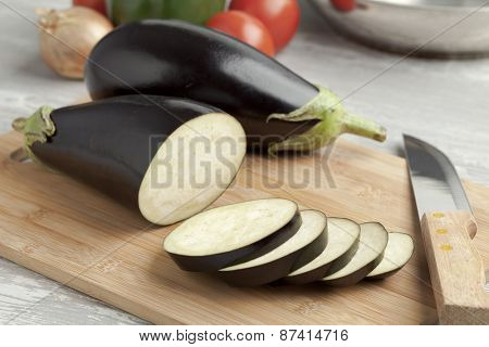 Fresh whole purple eggplants and slices on a cutting board