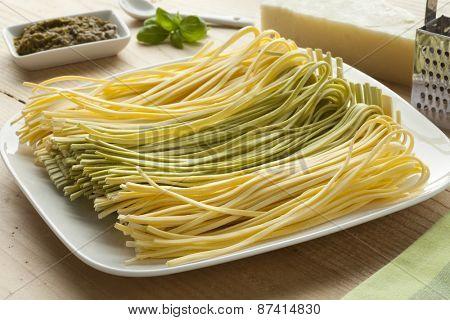 Fresh Tagliolini bicolore on a dish with pesto,basil leaves and pecorino cheese