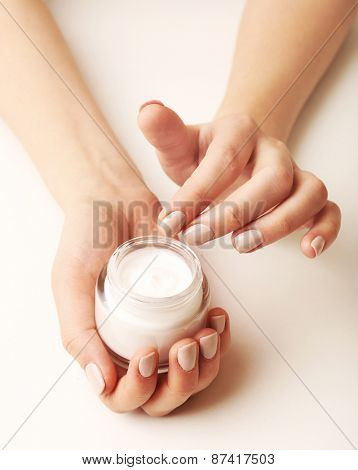 Female hands holding jar of cream isolated on white