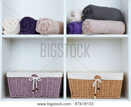 Rolled towels with wicker baskets on shelf of rack background