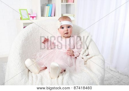 Cute baby girl in pink dress sitting in arm-chair, on home interior background