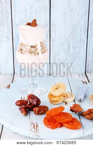 Glass of cream with oatmeal and almonds on color wooden background