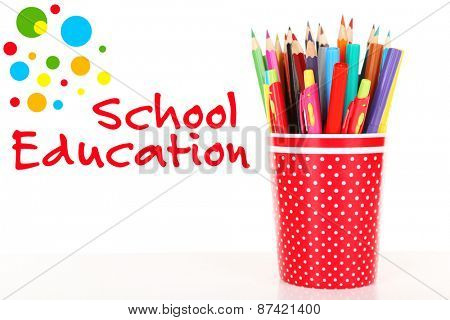 Colorful pens, pencils and markers in red polka-dot plastic cup isolated on white