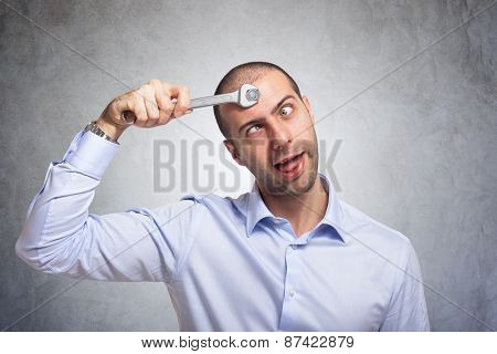 Funny man using a wrench to fix his brain