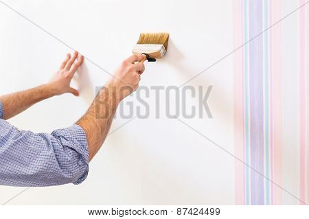 Handyman painting wall with background glue for a wallpaper