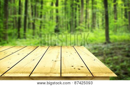 Empty wooden table on green background
