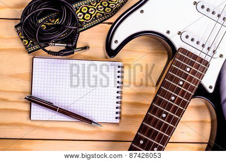electric guitar, memo pad on a wooden table.