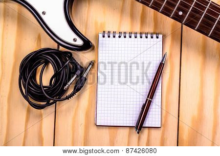 electric guitar and memo pad on wooden table