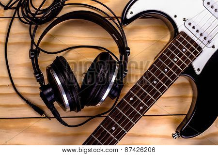 electric guitar and a professional grade headphones on wooden table