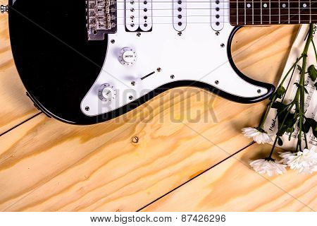 electric guitar and white flowers on wooden table.