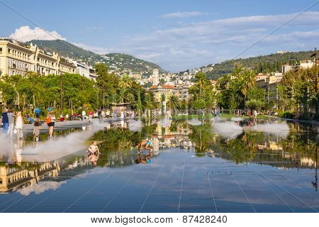 NICE, FRANCE - OCTOBER 2, 2014: Children playing in fountain on Promenade du Paillon reflecting the city and surrounding hills.