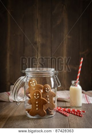 Gingerbread men in cookie jar with milk and straws in the background