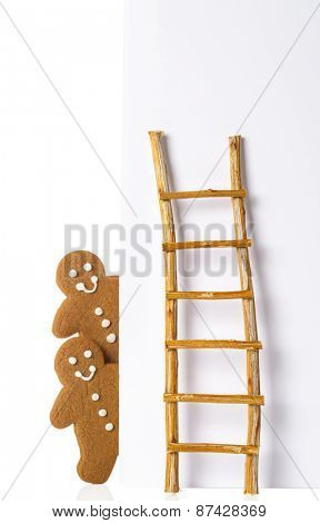 Gingerbread men against advertising board with ladder