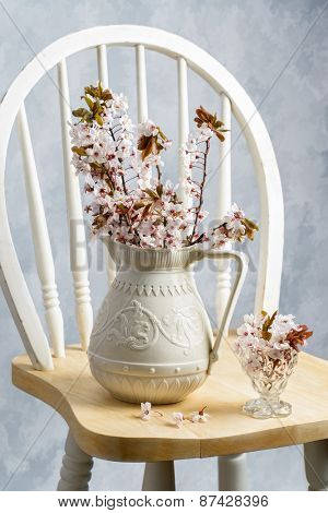 Antique jug filled with spring blossom on chair