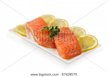 Salmon fillets with lemon slices on a white background