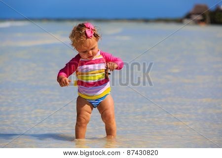 little girl holding starfish at summer beach