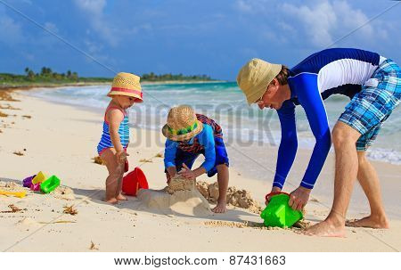 father and two kids playing with sand on summer beach