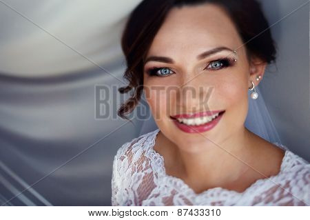 Portrait Of Young Bride In White Dress With Piercing