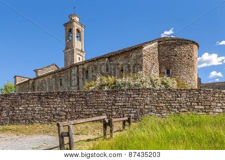 Old stone church under blue sky in town of Prunetto, Italy.