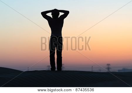 The man silhouette at sunset in desert with hands behind his head