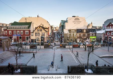 REYKJAVIK, ICELAND - MARCH 30, 2015: Young city dwellers ride on skateboards in the town center of Reykjavik on a winter evening, a lifestyle trend seen catching on in the young here.