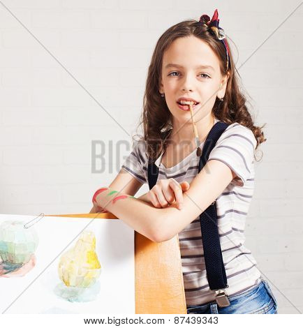 Cheerful child artist. Girl in classroom near easel