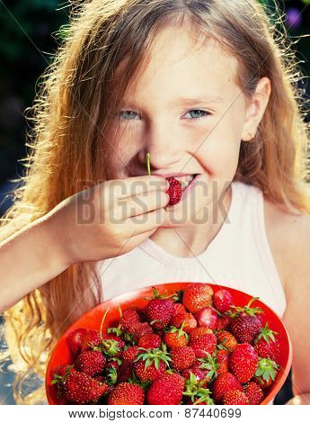 Child with strawberry. Girl with fruit, berry at garden