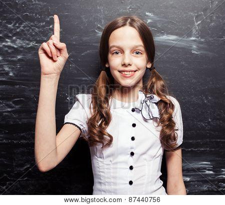 Girl near blackboard. Child at school. Student at classroom