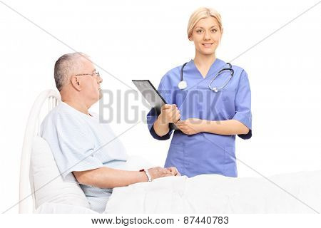 Female doctor holding a clipboard and standing next to a mature patient who is lying in hospital bed isolated on white background