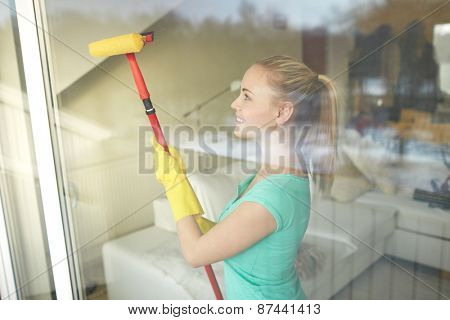 people, housework and housekeeping concept - happy woman in gloves cleaning window with sponge mop at home