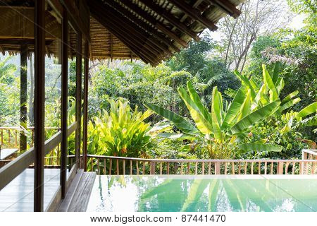 leisure, travel and tourism concept - swimming pool and bungalow at hotel resort