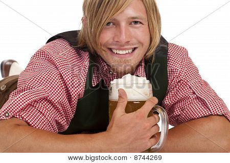 Happy man lying on floor holding oktoberfest beer stein.