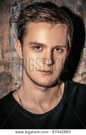 Close-up portrait of a handsome young man over grunge background. Men's beauty, fashion.