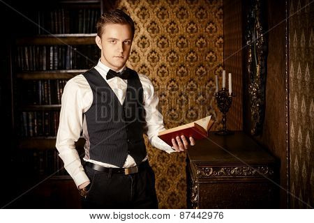 Handsome well-dressed man stands by the fireplace in a room with classic interior. Fashion.