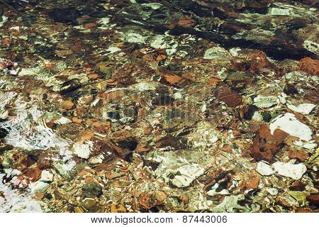 Clear Water Flowing Over Stones In The Creek