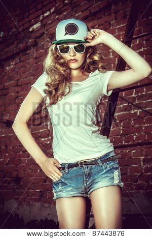 Beautiful modern girl near the brickwall. Youth style. Fashion shot.