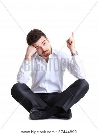 Portrait of business man sitting on the floor with shocked facial expression, isolated over white ba