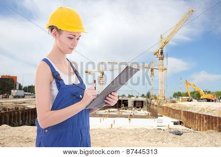 Young Attractive Woman Builder Writing Something In Clipboard