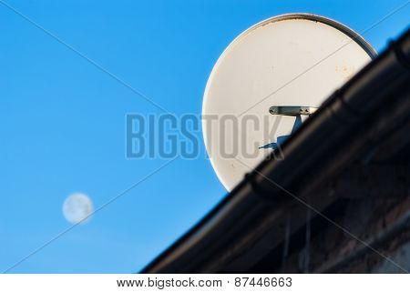 satellite dish on the roof on the background of the moon in the sky