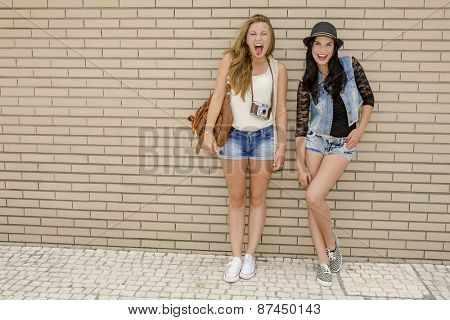 Two beautiful and young girlfriends having fun, in front of a brick wall