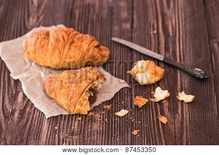 Croissant And Knife For Breakfast On A Dark Wooden Table